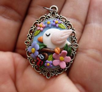 Ciondolo cameo decorato con fiori uccellino e coccinella in fimo fatti a mano